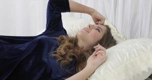 Jovem mulher que dorme na cama confortável em casa no meio do dia vídeos de arquivo