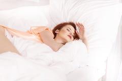 Jovem mulher que dorme na cama-roupa do branco na cama em casa fotografia de stock