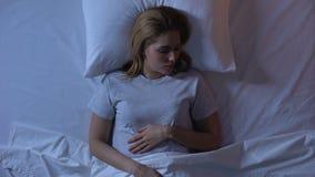 Jovem mulher que dorme pacificamente na cama confortável, qualidade do sono, parte-vista filme
