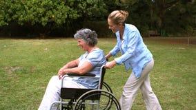 Jovem mulher que empurra sua mãe na cadeira de rodas filme