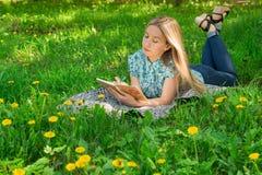 Jovem mulher que encontra-se e que escreve em seu diário na grama com flores Front View fotografia de stock royalty free
