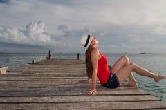 Jovem mulher que encontra-se e que aprecia o por do sol no mar Foto de Stock Royalty Free