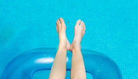 Jovem mulher que encontra-se e que toma sol na piscina imagens de stock royalty free