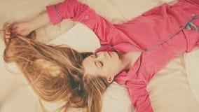Jovem mulher que encontra-se em pijamas vestindo da cama Fotografia de Stock