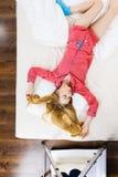 Jovem mulher que encontra-se em pijamas vestindo da cama imagem de stock royalty free