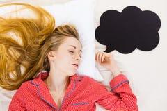 Jovem mulher que encontra-se em pijamas vestindo da cama Fotos de Stock Royalty Free
