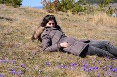Jovem mulher que encontra-se em um prado completamente de açafrões roxos Fotos de Stock