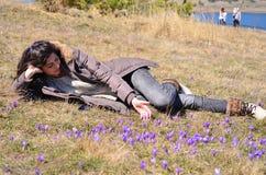 Jovem mulher que encontra-se em um prado completamente de açafrões roxos Foto de Stock Royalty Free