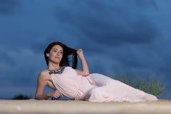 Jovem mulher que encontra-se em uma duna de areia Fotos de Stock Royalty Free