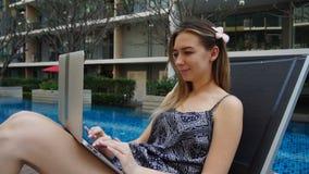 Jovem mulher que encontra-se na cadeira de praia e que usa o portátil perto da piscina vídeos de arquivo