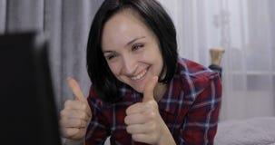 Jovem mulher que encontra-se na cama e que tem o bate-papo video usando a c?mara web no laptop foto de stock royalty free