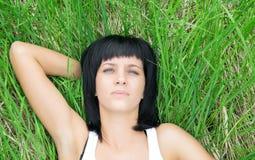 Jovem mulher que encontra-se na grama Imagem de Stock