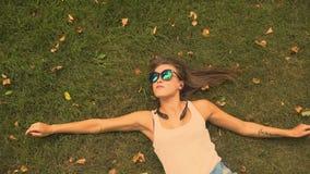 Jovem mulher que encontra-se na grama do parque video estoque