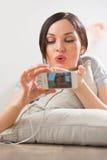 Jovem mulher que encontra-se no assoalho com seu telefone que toma imagens Imagens de Stock