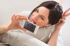 Jovem mulher que encontra-se no assoalho que toma imagens e selfies Fotos de Stock