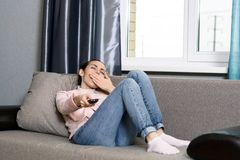 Jovem mulher que encontra-se no sofá com um controlo a distância da tevê e bocejos do enfado imagem de stock