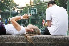 Jovem mulher que encontra-se para baixo no parque usando um smartphone com um outro homem imagem de stock royalty free