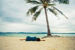 Jovem mulher que encontra-se sob a palmeira na praia Imagens de Stock Royalty Free