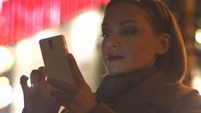 Jovem mulher que enrola a aplicação do smartphone no fundo iluminado do quadro de avisos video estoque