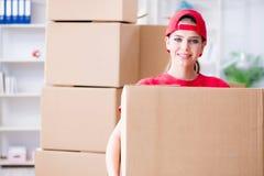 A jovem mulher que entrega caixas de efeitos pessoais fotos de stock royalty free