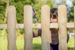 Jovem mulher que enverniza uma cerca com uma escova Foto de Stock