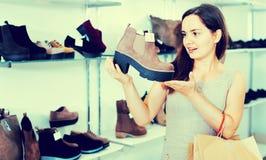 Jovem mulher que escolhe botas da queda na loja de sapatas Fotografia de Stock Royalty Free