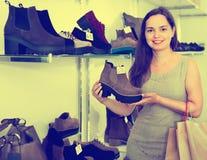 Jovem mulher que escolhe botas da queda na loja de sapatas Fotografia de Stock