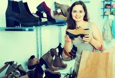 Jovem mulher que escolhe botas da queda na loja de sapatas Foto de Stock Royalty Free