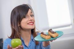 Jovem mulher que escolhe entre uma maçã e uma pastelaria do chocolate Fotografia de Stock
