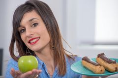 Jovem mulher que escolhe entre uma maçã e uma pastelaria do chocolate Imagens de Stock Royalty Free