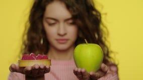 Jovem mulher que escolhe o bolo da ma?? pelo contr?rio para a nutri??o da dieta no est?dio vídeos de arquivo