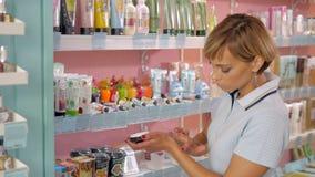 Jovem mulher que escolhe o creme cosmético na loja de beleza Imagens de Stock