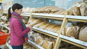 Jovem mulher que escolhe o pão no supermercado filme