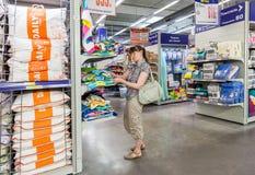 Jovem mulher que escolhe o roupa de cama na compra no METRO do hipermercado Foto de Stock