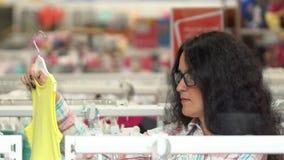 Jovem mulher que escolhe a roupa das crianças para a criança na loja da loja do bebê na alameda Compra da família, mãe que olha,  vídeos de arquivo