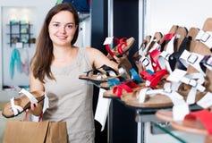 Jovem mulher que escolhe sapatas na loja Foto de Stock Royalty Free