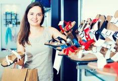 Jovem mulher que escolhe sapatas na loja Imagens de Stock Royalty Free