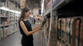 Jovem mulher que escolhe uma garrafa do suco de frutos no supermercado, mãe nova da mamã na loja Fotografia de Stock Royalty Free