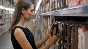 Jovem mulher que escolhe uma garrafa do suco de frutos no supermercado, mãe nova da mamã na loja Fotos de Stock Royalty Free
