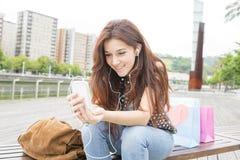 Jovem mulher que escuta a música com os fones de ouvido na rua foto de stock royalty free