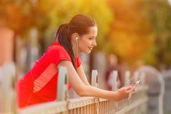 Jovem mulher que escuta a música durante o dia ensolarado na cidade imagens de stock