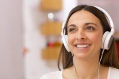 Jovem mulher que escuta a música em casa Foto de Stock