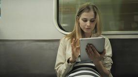 Jovem mulher que escuta a música no trem usando o tablet pc, menina do estudante após lições no vagão do metro com PC do portátil vídeos de arquivo