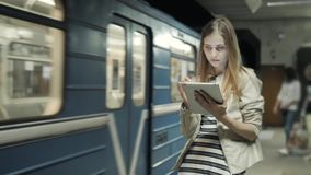 Jovem mulher que escuta a música no trem usando o tablet pc, menina do estudante após lições no vagão do metro com PC do portátil filme