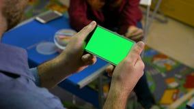 Jovem mulher que escuta um homem que fala e que guarda um telefone esperto com tela verde video estoque