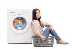 Jovem mulher que espera a lavanderia fotos de stock