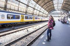 Jovem mulher que espera o trem na estação central Amsterdão fotografia de stock
