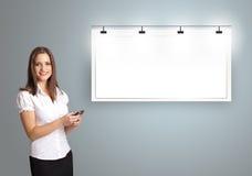 Jovem mulher que está ao lado de um espaço moderno da cópia e que guarda um p imagem de stock