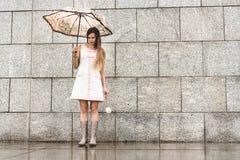 Jovem mulher que está apenas ao lado da parede do granito Fotografia de Stock Royalty Free