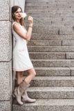 Jovem mulher que está apenas ao lado da parede do granito Fotos de Stock Royalty Free